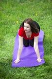 做瑜伽的女孩在公园 免版税库存照片