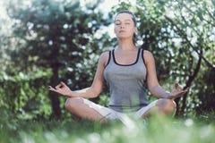 做瑜伽的女孩在公园 库存照片