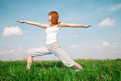 做瑜伽的女孩在公园 免版税库存图片