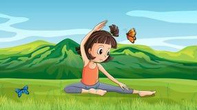 做瑜伽的女孩在小山附近 免版税库存照片