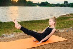 做瑜伽的女孩在日落由劈裂 免版税库存图片