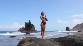 做瑜伽的女孩平衡在站立在石头的一条腿 给蒲公英领域开花的长发头脑和平松弛白人妇女年轻人穿衣 健康生活方式 平衡和和谐 股票录像