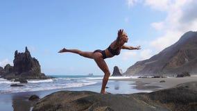 做瑜伽的女孩平衡在站立在石头的一条腿 给蒲公英领域开花的长发头脑和平松弛白人妇女年轻人穿衣 健康生活方式 平衡和和谐,和平 股票录像