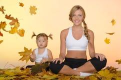 做瑜伽的妇女和孩子在叶子下 免版税库存图片