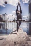 做瑜伽的妇女在城市布局的,巴黎湖附近 免版税库存照片