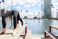 做瑜伽的妇女在城市布局的,巴黎湖附近 免版税图库摄影