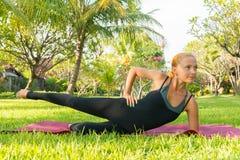 做瑜伽的妇女在庭院里 免版税库存图片