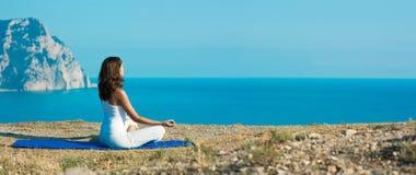 做瑜伽的妇女在海洋附近 免版税图库摄影