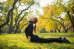 做瑜伽的妇女在秋天公园 图库摄影