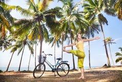 做瑜伽的妇女在自行车附近 免版税库存图片