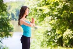 做瑜伽的妇女室外 免版税库存照片