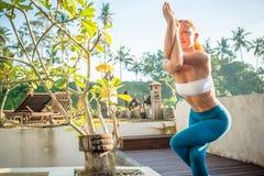 做瑜伽的妇女早晨 免版税库存照片