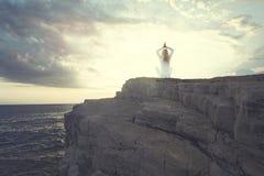 做瑜伽的妇女寻找在海洋前面的内在平衡 图库摄影