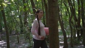 做瑜伽的孕妇 女孩在有一个地毯的公园走在她的手上,握她的在她的肚子的其他手 影视素材