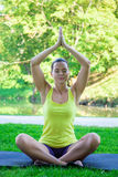 做瑜伽的少妇在夏天公园 免版税库存照片