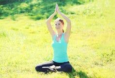 做瑜伽的少妇在夏日行使坐草 免版税库存照片