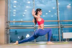 做瑜伽的少妇在席子行使在健身房 库存图片