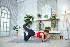 做瑜伽的少妇在早晨公园 免版税库存照片