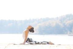 做瑜伽的少妇在湖附近户外,凝思 体育健身和行使本质上 秋天森林罗马尼亚日落 免版税图库摄影