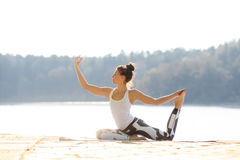 做瑜伽的少妇在湖附近户外,凝思 体育健身和行使本质上 秋天森林罗马尼亚日落 免版税库存照片