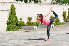 做瑜伽的年轻人、适合和运动的妇女行使室外 健身,体育,都市和健康生活方式概念 库存照片