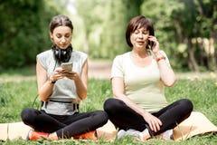 做瑜伽的年轻和老妇人在公园 免版税库存图片