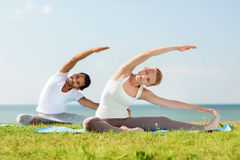 做瑜伽的微笑的夫妇行使户外 免版税库存图片