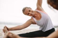 做瑜伽的微笑的妇女坐海滩 免版税库存图片