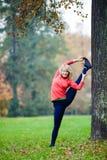 做瑜伽的愉快的少妇在公园 库存图片
