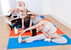 做瑜伽的教练员和资深顾客 库存照片