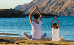 做瑜伽的母亲和女儿在海滩行使 免版税库存图片