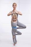 做瑜伽的母亲和女儿行使,健身,佩带同样舒适的田径服,家庭体育,体育的健身房被配对的holdin 免版税库存图片