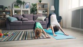 做瑜伽的母亲和小儿子在家一起放松享受活动 股票录像