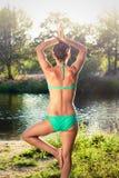 做瑜伽的比基尼泳装的女孩在河旁边在日落 免版税库存图片