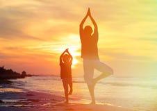 做瑜伽的父亲和儿子在日落 库存照片