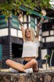 做瑜伽的白色T恤杉的美丽的白肤金发的女孩 妇女有的` s手纹身花刺 都市的方式 免版税库存照片