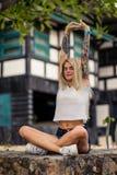 做瑜伽的白色T恤杉的美丽的白肤金发的女孩 妇女有的` s手纹身花刺 都市的方式 库存照片