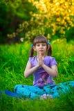 做瑜伽的美丽的女孩户外在绿草 库存图片
