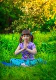 做瑜伽的美丽的女孩户外在绿草 图库摄影