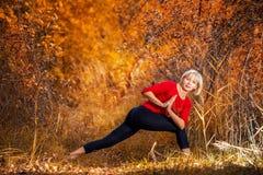做瑜伽的美丽的妇女户外在秋天 免版税库存图片