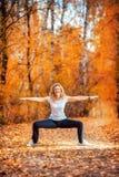 做瑜伽的美丽的妇女户外在秋天 免版税库存照片