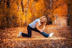 做瑜伽的美丽的妇女户外在秋天 库存照片