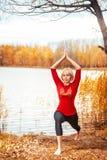 做瑜伽的美丽的妇女户外在秋天 图库摄影