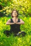 做瑜伽的美丽的妇女户外在绿草 库存图片