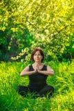 做瑜伽的美丽的妇女户外在绿草 免版税库存照片