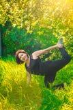 做瑜伽的美丽的妇女户外在绿草 免版税库存图片