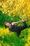 做瑜伽的美丽的妇女户外在绿草 图库摄影