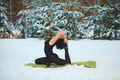 做瑜伽的美丽的妇女户外在雪 免版税图库摄影