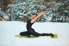 做瑜伽的美丽的妇女户外在雪 免版税库存图片