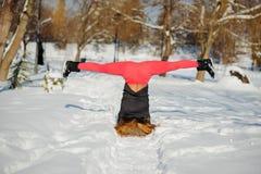 做瑜伽的美丽的妇女户外在雪 库存图片